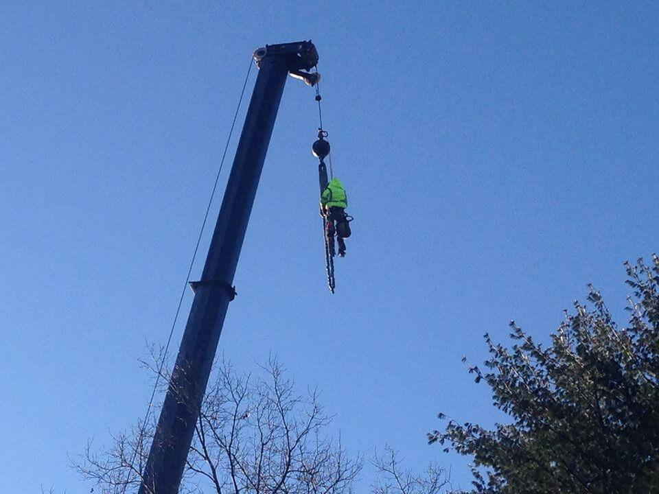 man hoisted up on crane